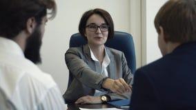 Επιχειρηματίες στο γραφείο που προγραμματίζει την κοινή αμοιβαία επωφελή συνεργασία και που υπογράφει τη σύμβαση Κινηματογράφηση  φιλμ μικρού μήκους