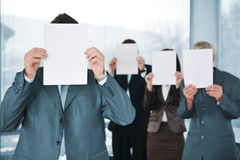 Επιχειρηματίες τεσσάρων που κρατούν το κενό έγγραφο Στοκ Εικόνα