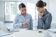 Επιχειρησιακές γυναίκες που εργάζονται μαζί σε μια ταμπλέτα Στοκ Εικόνες