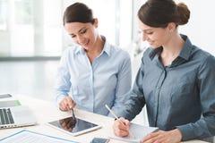 Επιχειρησιακές γυναίκες που εργάζονται μαζί σε μια ταμπλέτα Στοκ Εικόνα