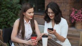 Επιχειρησιακές γυναίκες που κάθονται σε έναν θερινούς καφέ και μια ομιλία το κορίτσι παρουσιάζει κάτι στο φίλο της στην οθόνη sma φιλμ μικρού μήκους