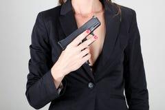 Επιχειρησιακές γυναίκες που κρατούν το μαύρο πυροβόλο όπλο Στοκ Φωτογραφία