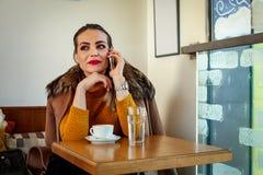 Επιχειρησιακές γυναίκες που μιλούν στη συνεδρίαση smartphone στο café Στοκ εικόνες με δικαίωμα ελεύθερης χρήσης