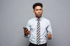 Επιχειρησιακή έννοια - αγχωτικός επιχειρηματίας αφροαμερικάνων που φωνάζει και που κραυγάζει στο κινητό τηλέφωνο Στοκ Φωτογραφία