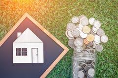 Επιχειρησιακή έννοια δανείου σπιτιών με την πτώση νομισμάτων από το βάζο γυαλιού και ho Στοκ φωτογραφία με δικαίωμα ελεύθερης χρήσης