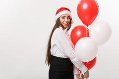 Επιχειρησιακή έννοια - η όμορφη νέα βέβαια επιχειρησιακή γυναίκα με το μπαλόνι εκμετάλλευσης καπέλων santa γιορτάζει για τα Χριστ Στοκ εικόνες με δικαίωμα ελεύθερης χρήσης