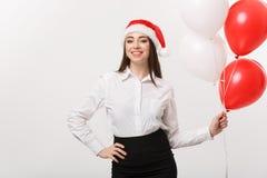Επιχειρησιακή έννοια - η όμορφη νέα βέβαια επιχειρησιακή γυναίκα με το μπαλόνι εκμετάλλευσης καπέλων santa γιορτάζει για τα Χριστ Στοκ Φωτογραφία