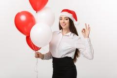 Επιχειρησιακή έννοια - η όμορφη νέα βέβαια επιχειρησιακή γυναίκα με το μπαλόνι εκμετάλλευσης καπέλων santa γιορτάζει για τα Χριστ Στοκ φωτογραφίες με δικαίωμα ελεύθερης χρήσης