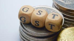 Επιχειρησιακή έννοια με μια λέξη GST στα συσσωρευμένα νομίσματα Στοκ Φωτογραφία