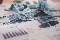 Επιχειρησιακή έννοια με τα χρήματα και τη γραφική παράσταση εγγράφων στον εργασιακό χώρο Στοκ Εικόνες