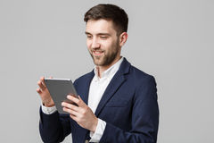 Επιχειρησιακή έννοια - όμορφο επιχειρησιακό άτομο πορτρέτου που παίζει την ψηφιακή ταμπλέτα με το βέβαιο πρόσωπο χαμόγελου Άσπρη  Στοκ Φωτογραφία