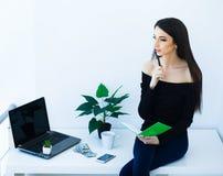 Επιχειρησιακή γυναίκα γραφείων που χαμογελά και που κάθεται στον πίνακα Ο Δρ γυναικών Στοκ Φωτογραφίες
