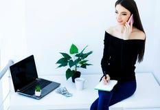 Επιχειρησιακή γυναίκα γραφείων που χαμογελά και που κάθεται στον πίνακα Ο Δρ γυναικών Στοκ Εικόνες