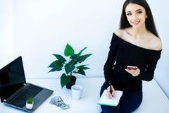 Επιχειρησιακή γυναίκα γραφείων που χαμογελά και που κάθεται στον πίνακα Ο Δρ γυναικών Στοκ εικόνα με δικαίωμα ελεύθερης χρήσης