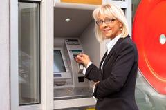 Επιχειρησιακή γυναίκα εκτός από το ATM Στοκ Φωτογραφία