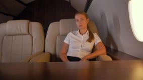 Επιχειρησιακή γυναίκα κοντά στο παράθυρο παραφωτίδων αεροσκαφών πρώτης θέσης φιλμ μικρού μήκους