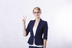 Επιχειρησιακή γυναίκα με τα γυαλιά στο σακάκι που παρουσιάζει δύο δάχτυλα Στοκ εικόνες με δικαίωμα ελεύθερης χρήσης