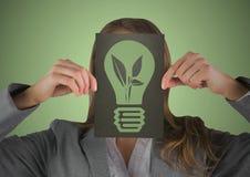 Επιχειρησιακή γυναίκα με τη μαύρη κάρτα πέρα από το πρόσωπο που παρουσιάζει πράσινο lightbulb γραφικό στο πράσινο κλίμα Στοκ φωτογραφία με δικαίωμα ελεύθερης χρήσης
