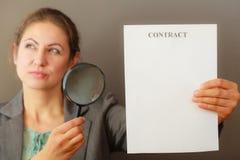 Επιχειρησιακή γυναίκα με τη σύμβαση και loupe Στοκ Φωτογραφίες