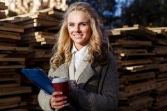 Επιχειρησιακή γυναίκα με τον καφέ στην εργασία Επιθεώρηση της ξυλείας στοκ εικόνα με δικαίωμα ελεύθερης χρήσης