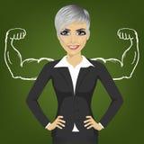 Επιχειρησιακή γυναίκα με τους ισχυρούς μυς βραχιόνων για την επιτυχία που στέκεται με τα χέρια στα ισχία Στοκ Εικόνες