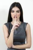 Επιχειρησιακή γυναίκα με το δάχτυλο στα χείλια της στοκ φωτογραφίες