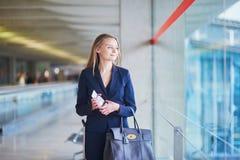 Επιχειρησιακή γυναίκα με το διαβατήριο και πέρασμα τροφής στο διεθνή αερολιμένα Στοκ Εικόνες
