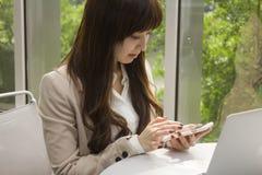 Επιχειρησιακή γυναίκα με το κινητό τηλέφωνο που λειτουργεί μπροστά από το φορητό προσωπικό υπολογιστή Στοκ Εικόνες