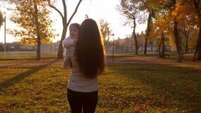 Επιχειρησιακή γυναίκα με το μικρό περπάτημα παιδιών μέσω του πάρκου πόλεων στις ακτίνες ηλιοβασιλέματος του ήλιου φιλμ μικρού μήκους