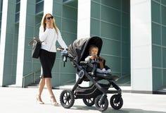 Επιχειρησιακή γυναίκα με το περπάτημα μεταφορών μωρών Στοκ Φωτογραφία
