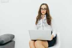 Επιχειρησιακή γυναίκα με το σημειωματάριο στο γραφείο στην καρέκλα Στοκ Φωτογραφία