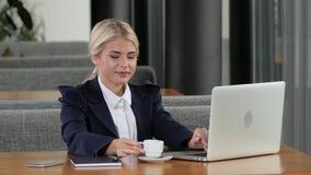 Επιχειρησιακή γυναίκα με το χαμόγελο που εργάζεται σε ένα lap-top σε έναν καφέ απόθεμα βίντεο