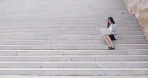 Επιχειρησιακή γυναίκα με το lap-top στα σκαλοπάτια απόθεμα βίντεο