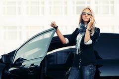 Επιχειρησιακή γυναίκα μόδας στα γυαλιά ηλίου που μιλούν στο τηλέφωνο κυττάρων εκτός από ένα αυτοκίνητό της Στοκ Φωτογραφία