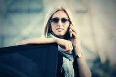 Επιχειρησιακή γυναίκα μόδας στα γυαλιά ηλίου που μιλούν στο τηλέφωνο κυττάρων έξω από το αυτοκίνητό της Στοκ Φωτογραφία