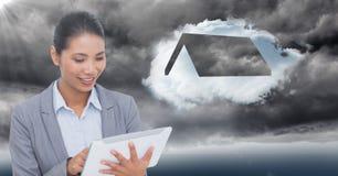 Επιχειρησιακή γυναίκα πίσω από τη φλόγα με την ταμπλέτα και το σύννεφο με τη στέγη ενάντια στο θυελλώδη ουρανό Στοκ Φωτογραφία