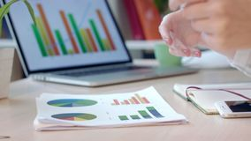 Επιχειρησιακή γυναίκα που αναλύει τα οικονομικά διαγράμματα στο γραφείο Ανάλυση επιχειρησιακών εγγράφων απόθεμα βίντεο