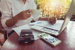 Επιχειρησιακή γυναίκα που αναλύει το έγγραφο γραφικών παραστάσεων με το lap-top και που κρατά τον εκλεκτής ποιότητας τόνο καφέ Στοκ Φωτογραφία
