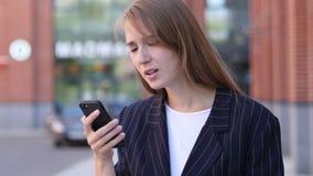 Επιχειρησιακή γυναίκα που αντιδρά στην απώλεια χρησιμοποιώντας Smatphone έξω από το γραφείο απόθεμα βίντεο