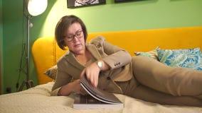 Επιχειρησιακή γυναίκα που βγάζει φύλλα μέσω ενός περιοδικού, που βγάζει τα γυαλιά απόθεμα βίντεο