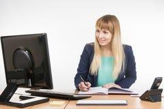 Επιχειρησιακή γυναίκα που γράφει σε ένα επιχειρησιακό βιβλίο και που εξετάζει το όργανο ελέγχου υπολογιστών Στοκ Εικόνες