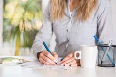 Επιχειρησιακή γυναίκα που γράφει στο έγγραφο με τη μάνδρα στο γραφείο στο σύγχρονο γραφείο στοκ φωτογραφία