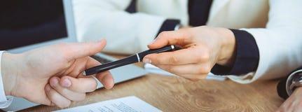 Επιχειρησιακή γυναίκα που δίνει τη μάνδρα στον επιχειρηματία έτοιμο να υπογράψει τη σύμβαση Επικοινωνία επιτυχίας στη συνεδρίαση  στοκ φωτογραφία με δικαίωμα ελεύθερης χρήσης