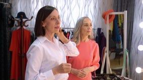 Επιχειρησιακή γυναίκα που δοκιμάζει τα σκουλαρίκια στο κατάστημα εξαρτημάτων και που κοιτάζει στον καθρέφτη Πωλητής που βοηθά να  απόθεμα βίντεο