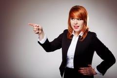 Επιχειρησιακή γυναίκα που δείχνει το δάχτυλό της ενάντια σε κάποιο Στοκ Φωτογραφία