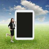 Επιχειρησιακή γυναίκα που δείχνει το μεγάλο τηλέφωνο ταμπλετών που παρουσιάζει στη χλόη Gra Στοκ εικόνα με δικαίωμα ελεύθερης χρήσης
