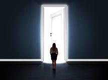 Επιχειρησιακή γυναίκα που εξετάζει τη μεγάλη φωτεινή ανοιγμένη πόρτα στοκ εικόνες
