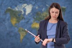 Επιχειρησιακή γυναίκα που εξετάζει το ρολόι Έννοια παγκοσμιοποίησης παγκόσμιων χαρτών Στοκ εικόνες με δικαίωμα ελεύθερης χρήσης