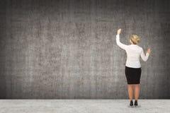 Επιχειρησιακή γυναίκα που επισύρει την προσοχή στον τοίχο Στοκ Εικόνες
