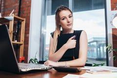 Επιχειρησιακή γυναίκα που εργάζεται στο γραφείο που εξετάζει τη κάμερα στοκ φωτογραφία με δικαίωμα ελεύθερης χρήσης